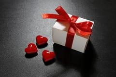 Cadeau du ` s de Valentine avec le ruban rouge et les coeurs en verre Images stock