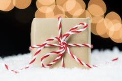 Cadeau emballé en papier de vintage avec la ficelle rouge et blanche sur la neige Images stock