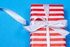 Cadeau en emballage rouge et blanc avec le ruban Images stock