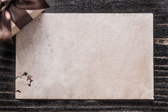 Cadeau enfermé dans une boîte avec le papier d'arc sur le panneau en bois de vintage Photos stock
