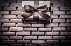 Cadeau enfermé dans une boîte avec le ruban sur les nattes en osier en bois Images libres de droits