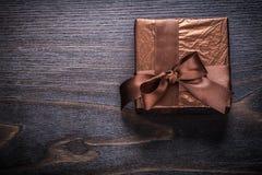Cadeau enfermé dans une boîte enveloppé en papier scintillant sur le panneau en bois de vintage Images libres de droits