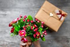 Cadeau enveloppé un fond, un jour gris en bois de valentines, photos romantiques, bouquet romantique avec des coeurs et cadeaux,  Photos libres de droits