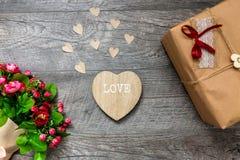 Cadeau enveloppé un fond, un jour gris en bois de valentines, photos romantiques, bouquet romantique avec des coeurs et cadeaux,  Photo stock