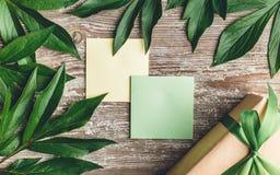Cadeau et autocollant sur un vieux conseil avec des feuilles de vert autour de l'ed Photos stock