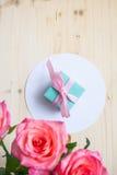 Cadeau et trois roses sur le fond blanc Image libre de droits