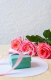 Cadeau et trois roses sur le fond blanc Images libres de droits