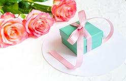 Cadeau et trois roses sur le fond blanc Photo stock