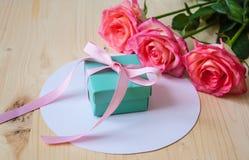 Cadeau et trois roses sur le fond blanc Photographie stock