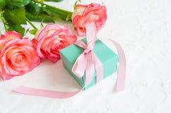 Cadeau et trois roses sur le fond blanc Photographie stock libre de droits