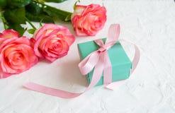 Cadeau et trois roses sur le fond blanc Photos libres de droits