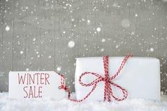 Cadeau, fond de ciment avec des flocons de neige, vente d'hiver des textes Photo stock