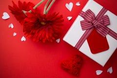 Cadeau, gerberas rouges et un coeur sur un fond rouge photo libre de droits