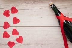 Cadeau, le coeur et la bouteille de vin rouge pendant un jour romantique du ` s de Valentine de vacances image libre de droits