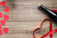 Cadeau, le coeur et la bouteille de vin rouge pendant un jour romantique du ` s de Valentine de vacances images libres de droits