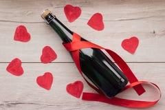 Cadeau, le coeur et la bouteille de vin rouge pendant un jour romantique du ` s de Valentine de vacances photos stock