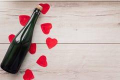 Cadeau, le coeur et la bouteille de vin rouge pendant un jour romantique du ` s de Valentine de vacances Image stock
