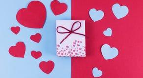 Cadeau ou boîte actuelle avec le ruban rouge d'arc et coeur de scintillement sur le fond rustique pour le jour de valentines Images stock