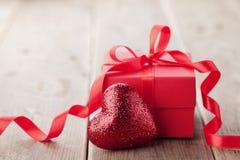 Cadeau ou boîte actuelle avec le ruban rouge d'arc et coeur de scintillement sur la table de vintage pour le jour de valentines Photo stock