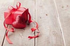 Cadeau ou boîte actuelle avec le ruban rouge d'arc et coeur de scintillement sur le fond en bois pour le jour de valentines Photos libres de droits