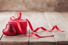 Cadeau ou boîte actuelle avec le ruban rouge d'arc et coeur de scintillement sur le fond rustique pour le jour de valentines Photo libre de droits