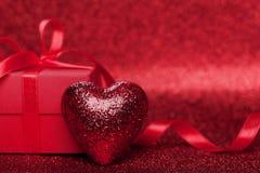 Cadeau ou boîte actuelle avec le ruban rouge d'arc et coeur sur le fond de scintillement pour le jour de valentines Photographie stock