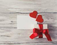 Cadeau ou boîte actuelle avec le ruban rouge d'arc et coeurs sur le Ba rustique Photographie stock