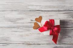 Cadeau ou boîte actuelle avec le ruban rouge d'arc et coeurs sur le Ba rustique Photographie stock libre de droits