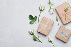 Cadeau ou boîte actuelle enveloppée en papier d'emballage et fleur rose sur la table grise d'en haut Dénommer plat de configurati Image libre de droits