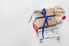 Cadeau ou boîte actuelle et jour de pères heureux de notes dans le caddie sur le fond clair Images stock