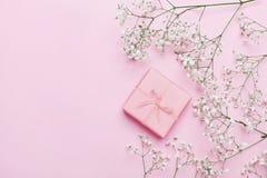 Cadeau ou boîte et fleur actuelles sur la table rose d'en haut Couleur en pastel Carte de voeux style plat de configuration Photo libre de droits