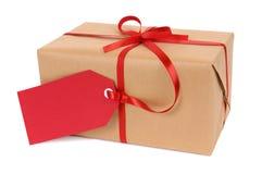 Cadeau ou colis de Noël attaché avec l'étiquette rouge de ruban et de cadeau d'isolement sur le fond blanc Images libres de droits
