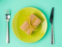 Cadeau, paquet de papier brun de Papier d'emballage avec le ruban d'or sur le pla jaune Photographie stock libre de droits