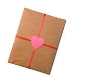 Cadeau pour le papier d'emballage de jour du ` s de Valentine attaché avec un ruban rouge avec un coeur d'isolement sur le fond b Photos stock