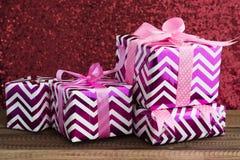 Cadeau/présent sur une table en bois avec le fond rouge brillant Images libres de droits