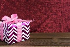 Cadeau/présent sur une table en bois avec le fond rouge brillant Images stock