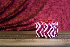 Cadeau/présent sur une table en bois avec le fond rouge brillant Photos libres de droits