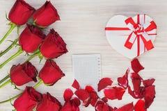 Cadeau, roses et papier de jour du ` s de Valentine sur le fond en bois. Photographie stock
