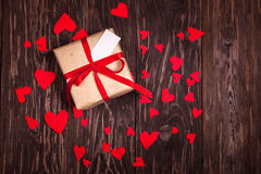 Cadeau rustique avec un ruban rouge sur le fond en bois Image libre de droits