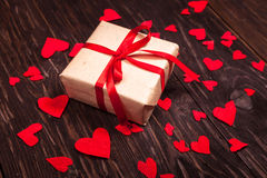 Cadeau rustique avec un ruban rouge sur le fond en bois Images libres de droits