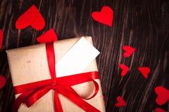 Cadeau rustique avec un ruban rouge sur le fond en bois Image stock