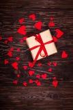 Cadeau rustique avec un ruban rouge sur le fond en bois Photo libre de droits
