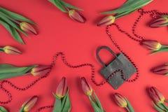 Cadeau, vente, concept de achat Composition en tulipes avec le panier de papier sur le fond rouge Configuration plate, vue supéri Photo libre de droits