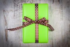 Cadeau vert pour Noël ou toute autre célébration sur la planche en bois Images stock