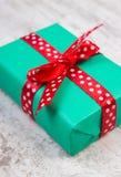 Cadeau vert pour Noël ou toute autre célébration sur la planche en bois Photo stock