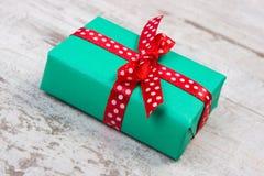 Cadeau vert pour Noël ou toute autre célébration sur la planche en bois Photographie stock libre de droits