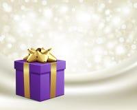 Cadeau violet avec la proue d'or sur la soie Photos stock