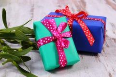Cadeaux colorés enveloppés pour Noël et le gui sur le vieux fond en bois Images stock