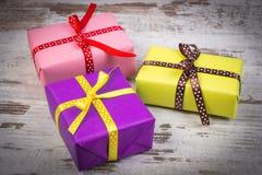 Cadeaux colorés enveloppés pour Noël ou toute autre célébration sur la vieille planche blanche Photo libre de droits