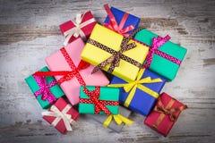 Cadeaux colorés enveloppés pour Noël ou toute autre célébration sur la vieille planche blanche Photos stock